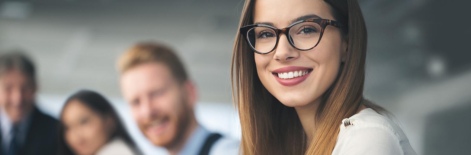 Smilende kvinne med tre medarbeidere