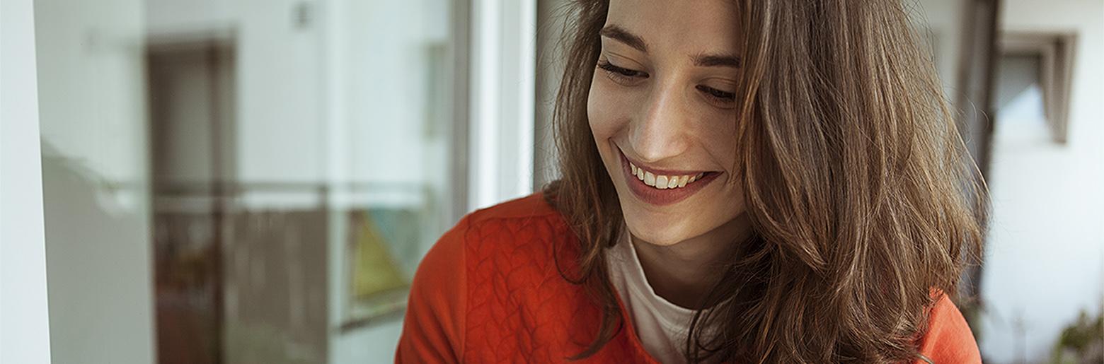 Ung smilende kvinne med rød genser