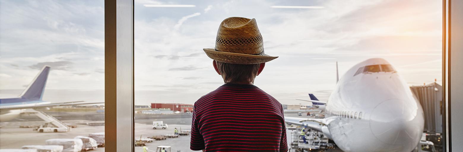 Gutt ser på fly på flyplass