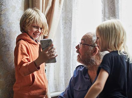 To barn og en eldre mann som ser på mobilen