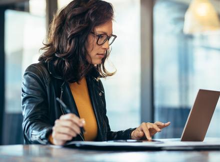 En kvinne sitter ved en pc og tar notater