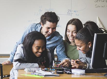 Lærer og elever ser på en robot