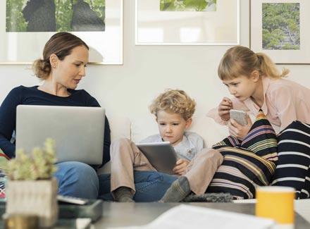 Mor og barn foran skjermer