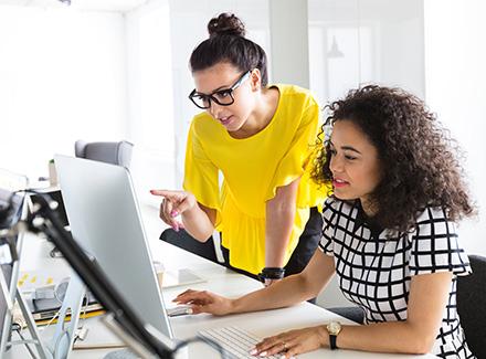 To kvinner ser på en skjerm