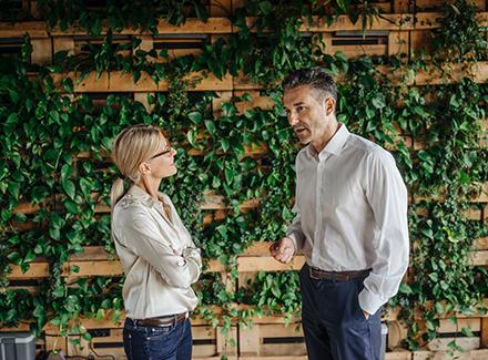 Illustrasjonsbilde_kollegaer snakker foran en vegg med planter