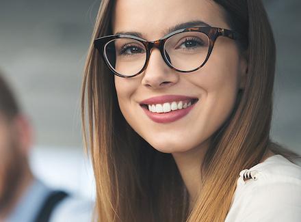 Blid kvinnelig medarbeider med briller