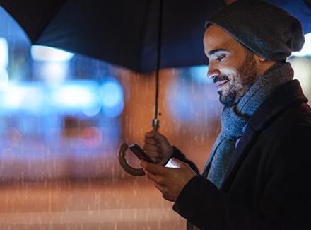 Mann med paraply og mobil