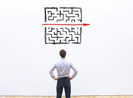 Mann ser på labyrint tegnet på veggen