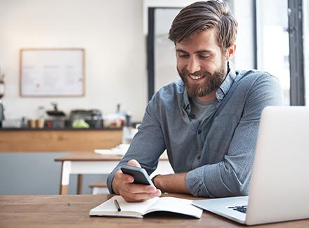Smilende mann foran PC med mobil