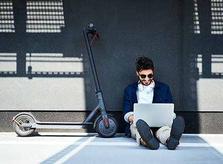 Ung mann med PC og sparkesykkel