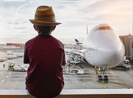Gutt ser på fly på en flyplass