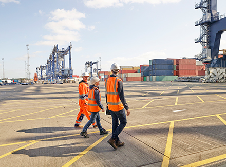 Team går på havna foran containere og kraner