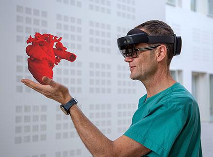 Lege Henrik Brun holder hologramhjerte i hånda
