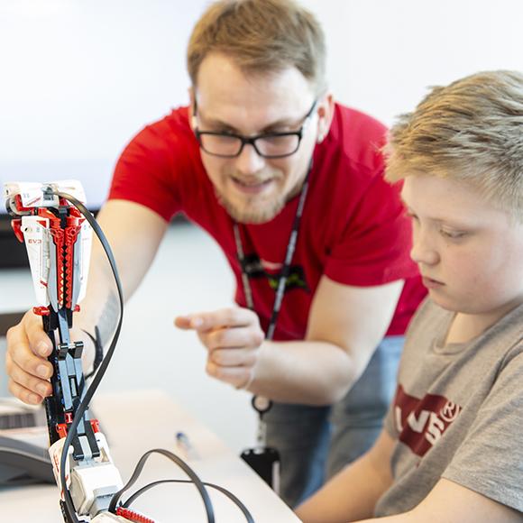 En voksen lærer et barn å kode