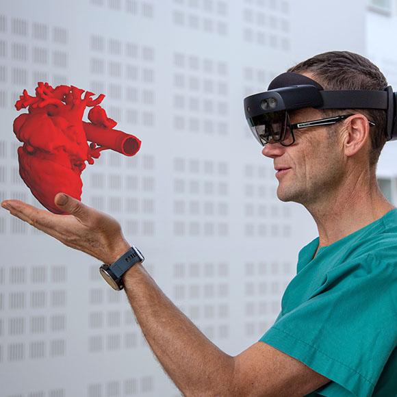 Lege holder hologram av hjerte i hånden